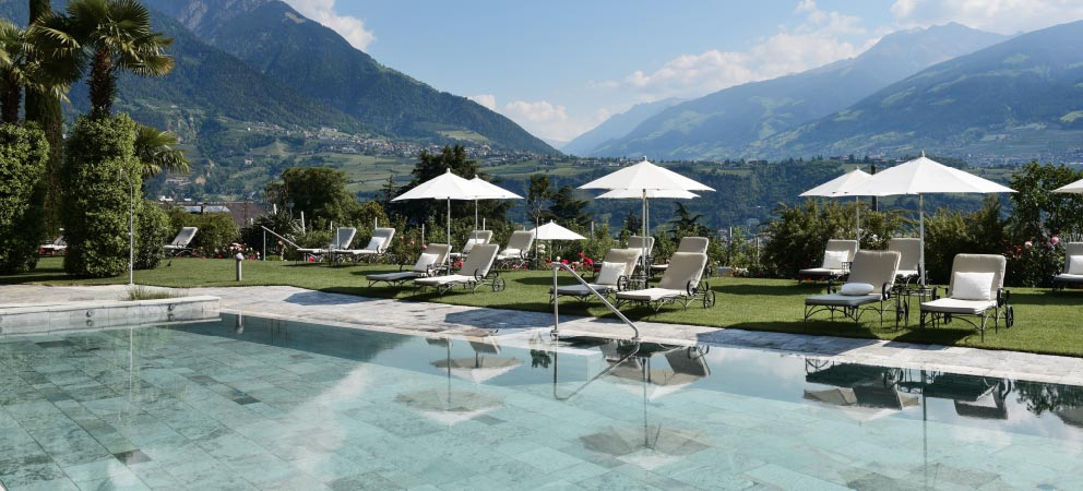 The swimming pool of Hotel Giardino Marling with a view of the mountains around Merano