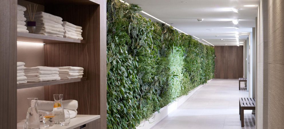 elegant corridor in the spa area of the Giardino Marling hotel with a green wall with plants; on the left a shelf with folded towels